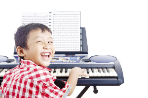 Portrait of little piano player smiling and playing the piano. shot in studio isolated on white