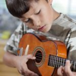 A young boy plays his ukulele